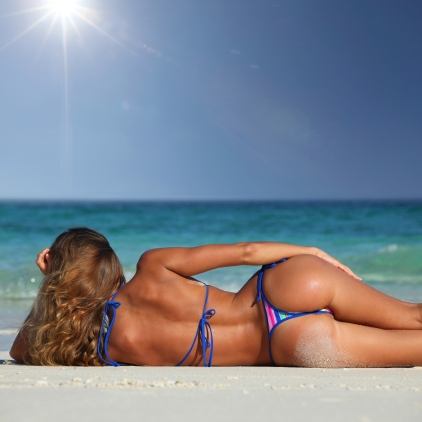 Rear view of sexy woman in bikni lying on topical beach