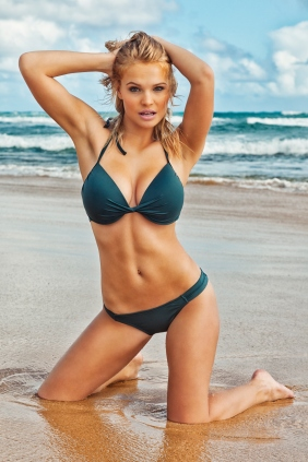 """Photo of a sexy young blonde woman in a dark green bikini with green trim, kneeling on a remote Hawaiian beach."""
