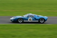 A classic Ford GT40 Le Mans racing car at high speed on the track.